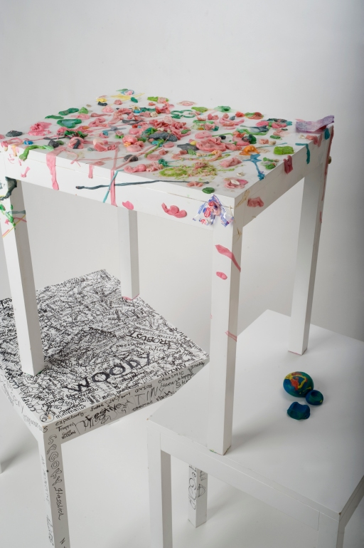 Interactive Tables. This is a series of three coffee tables that are catalysts for interaction and conversation. They transform over time and showcase their history. The first table was inspired by the habit of sticking gum under a table. Instead of placing gum under the table, users are encouraged to stick gum to its surface. The second table is similar to the first, but uses modeling clay instead of gum. Users can create sculptural elements on the table by playing with the modeling clay. The last table is a collective work of poetry. Users are encouraged to write creative and thought-provoking adjectives on its surface.